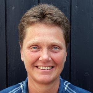 Porträtt på Cecilia Dalén som står mot en plank.